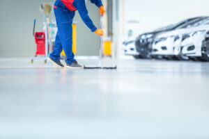 Car mechanic repair service center cleaning using mops to roll water from the epoxy floor. In the car repair service center